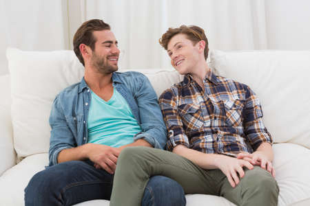 homosexual: Happy homosexual couple speaking together on sofa at home