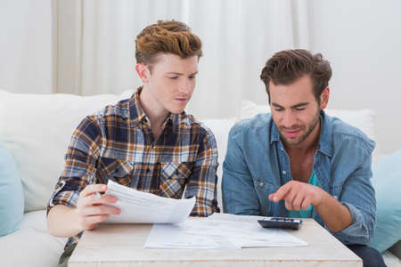 defeated: Defeated homosexual couple looking at bill at home