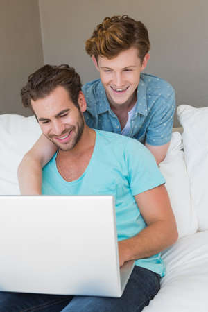 couple on couch: Cute homosexual couple using laptop on couch at home in the living room