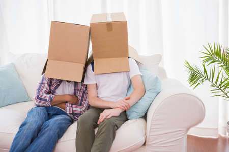 couple on couch: Homosexual couple wearing boxes over head on couch at home LANG_EVOIMAGES