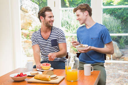 each other: Happy homosexual couple having breakfast and looking at each other at home LANG_EVOIMAGES