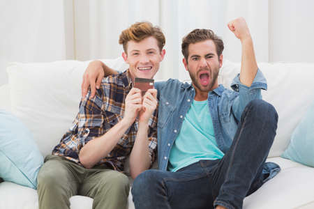 acclamation: Happy homosexual couple cheering on sofa at home
