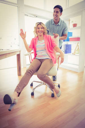 swivel chair: Smiling colleagues playing together with swivel chair in the office
