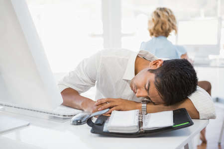 sleeping businessman: Young sleeping businessman with businesswoman in the background in the office