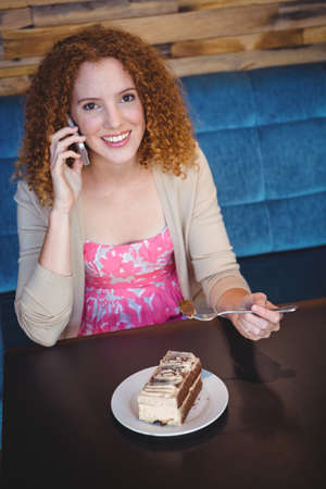 phoning: Happy pretty woman taking a piece of cake and phoning LANG_EVOIMAGES