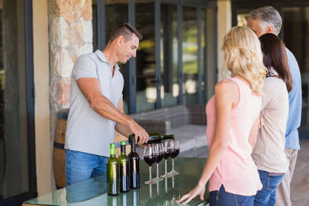 sommelier: Smiling sommelier pouring wine in front of customers at vineyard