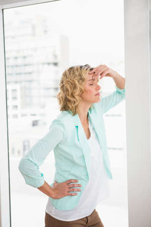 troubled: Troubled casual businesswoman leaning against wall in the office