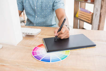 colour chart: Casual businessman working with digitizer and colour chart in the office