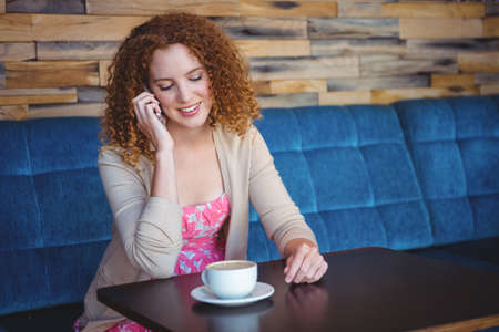 phoning: Portrait of a happy pretty woman taking a coffee and phoning LANG_EVOIMAGES