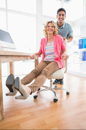 swivel: Portrait of smiling colleagues playing together with swivel chair in the office