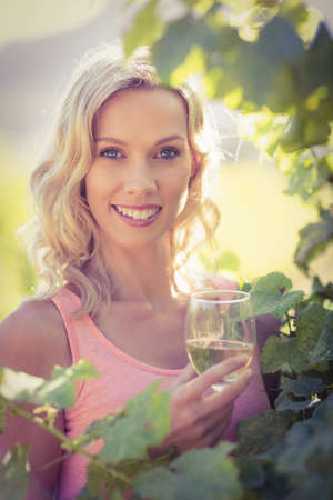 inbetween: Portrait of smiling woman with wineglass standing inbetween grapevine at vineyard LANG_EVOIMAGES
