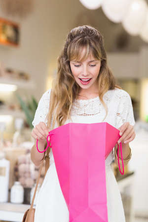 looking inside: Beautiful customer looking inside shopping bags in a beauty store LANG_EVOIMAGES