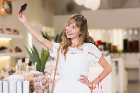 beauty store: Beautiful woman making selfie in a beauty store
