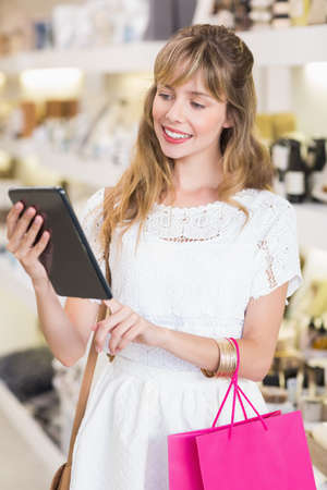 beauty store: Beautiful woman using her tablet in a beauty store