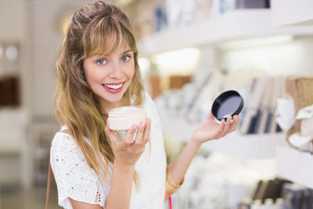 beauty store: Beautiful customer smelling product in a beauty store