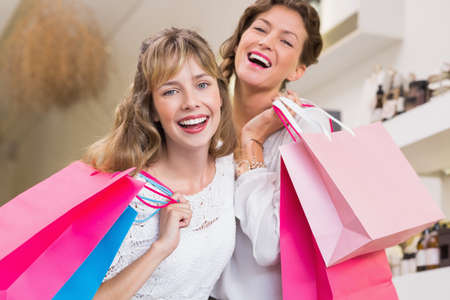beauty store: Beautiful women holding shopping bags laughing in a beauty store LANG_EVOIMAGES