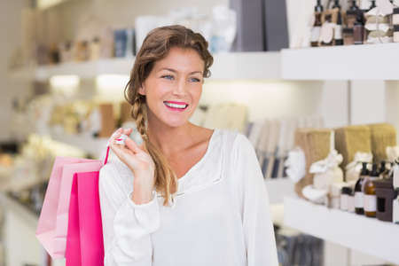 beauty store: Beautiful woman holding shopping bags in a beauty store