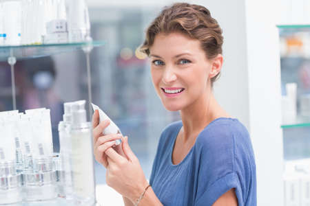 beauty store: Beautiful costumer holding product in a beauty store LANG_EVOIMAGES
