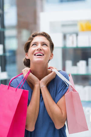 costumer: Beautiful costumer holding shopping bags in a beauty store LANG_EVOIMAGES