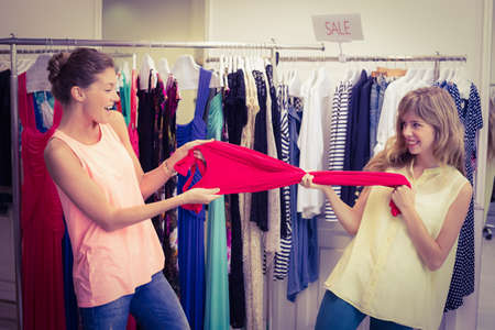 fighting styles: Friends pulling at dress in a fashion boutique LANG_EVOIMAGES
