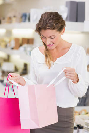 looking inside: Beautiful woman looking inside shopping bag in a beauty store LANG_EVOIMAGES