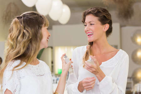 beauty store: Beautiful friends holding perfume in a beauty store LANG_EVOIMAGES