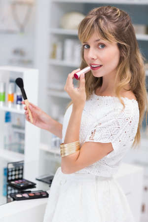 putting on: Beautiful costumer putting on makeup in a beauty store
