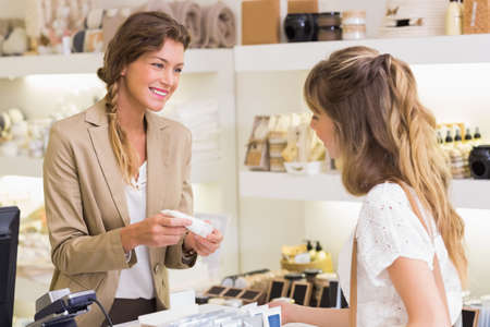 retailer: Beautiful employee and customer at cash register in a beauty store