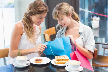 looking inside: Beautiful women sitting and looking inside shopping bag in the cafe
