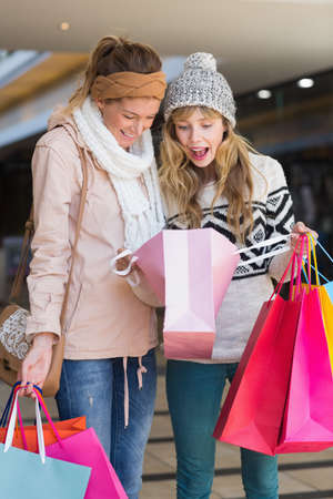looking inside: Smiling women looking inside shopping bags at the mall