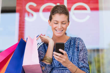 phone message: Smiling woman holding shopping bags looking at phone at the mall
