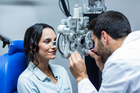 optician: Optician using a phoropter on his patient in a clinic LANG_EVOIMAGES