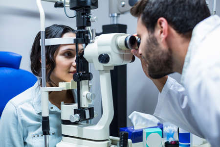 slit: Male optician examining womans eyes through slit lamp in clinic