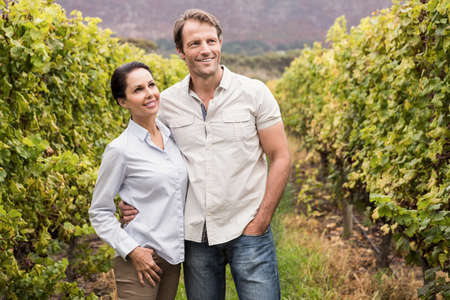 arms around: Smiling young couple with arms around in the winery