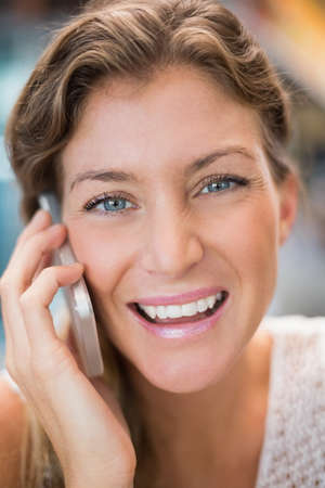 phoning: Beautiful woman having a phone call and smiling at the camera in the cafe