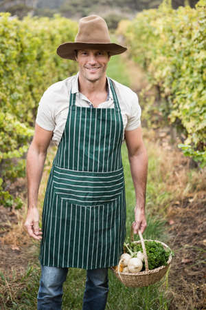 seasonal worker: Young happy farmer holding a basket of vegetables in the field LANG_EVOIMAGES