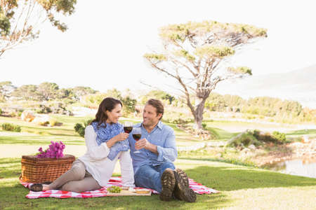 picknick: Cute couple drinking wine in a park for a pick-nick