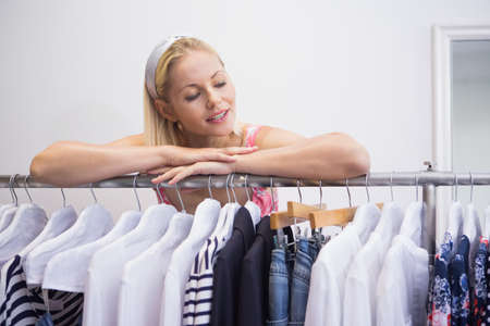 clothes rail: Pretty blonde smiling at camera by clothes rail in fashion boutique
