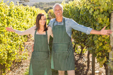 viticulture: Portrait of smiling couple presenting their viticulture in the grape fields