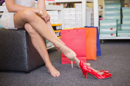 court shoes: Woman trying on court shoes  in a shoe shop LANG_EVOIMAGES