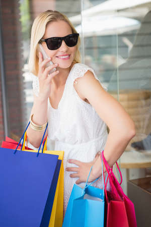phoning: Pretty blonde on the phone with shopping bags at the mall
