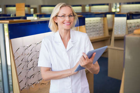 eye service: Optician using her tablet pc at the opticians store LANG_EVOIMAGES