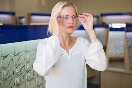 trying on: Pretty blonde trying on glasses at the opticians store