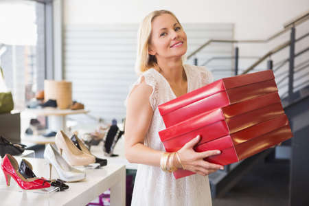 shoe boxes: Woman holding pile of shoe boxes in a shoe shop