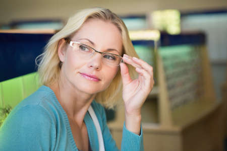 middleaged: Pretty blonde trying on glasses at the opticians store