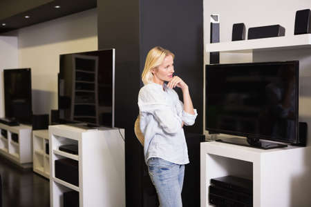 electronics store: Pretty blonde shopping for new television at the electronics store