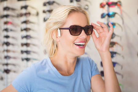 trying on: Pretty blonde trying on sunglasses at the opticians store