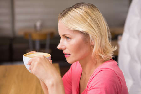 mid thirties: Pretty blonde having coffee in a cafe