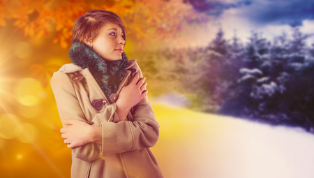 cold background: Thoughtful woman in winter coat against autumn changing to winter