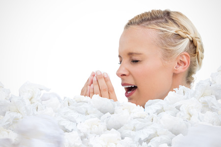 tissues: Blonde woman sneezing with hands in front of her face against used tissues